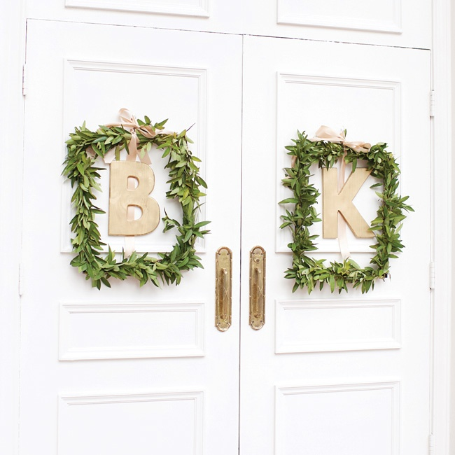 "As guests arrived they entered the sanctuary through large white double doors where gold scripted monogrammed letters ""B"" and ""K"" hung from a matte gold satin ribbon framed with fresh laureal leafs."