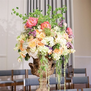 Gilded urns filled with hydrangeas, roses, lilacs, lilies and orchids flanked the altar.