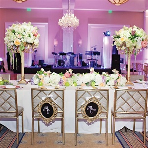 "Crystals were draped over all of the arrangements. ""I've always loved the romantic whimsical look of crystals hanging from branches,"" explains Kady. Two large candelabra centerpieces adorned the head table; multiple small floral arrangements and gilded pillar candle stands ran the length of it."
