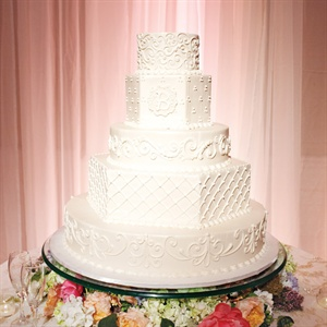 The five-tiered buttercream cake was adorned with piping, pearlized shimmer and the couple's logo.