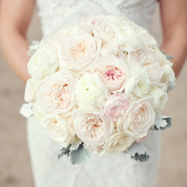The bride carried a rounded bouquet of blush and ivory roses that were finished with a subtle touch of greenery.