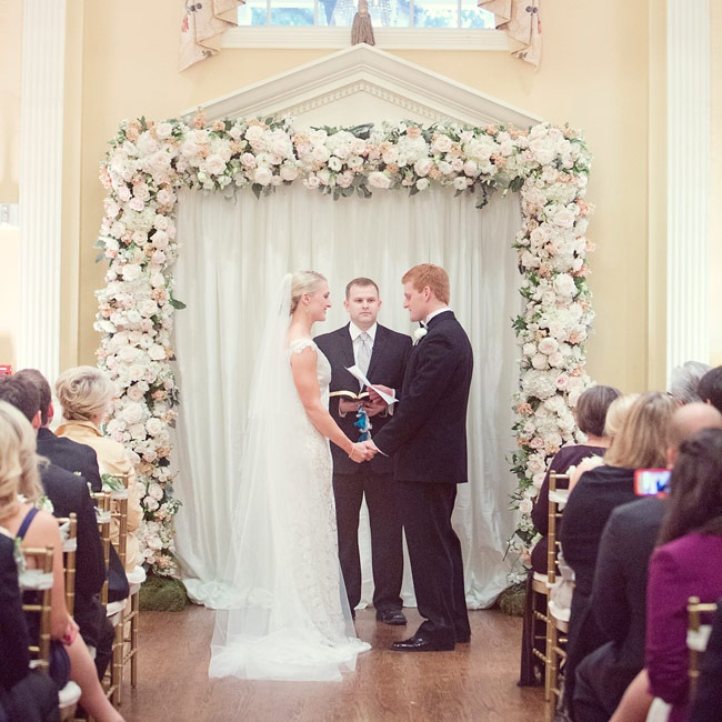 Although the ceremony had to be moved inside due to cold temperatures and rain, Arlington Hall's Great Hall provided a beautiful venue for the day's festivities. Two double doors were draped in off-white fabric and outlined with a lush garland of roses and greenery to create the altar.