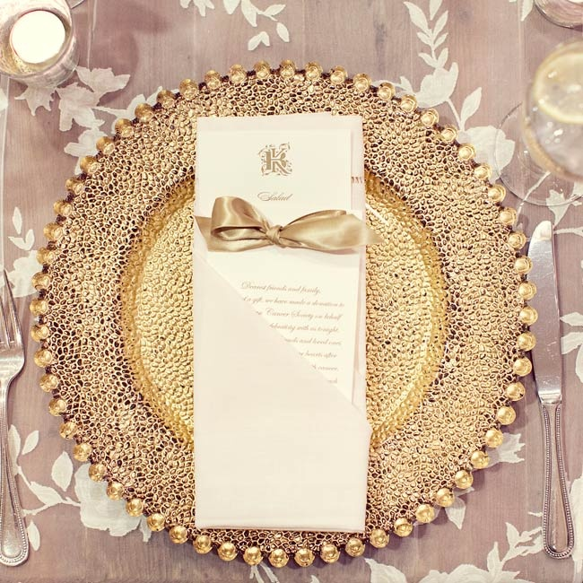 Delicate linens were topped with gold chargers and cream-and-gold menu cards, which included a note telling guests a donation had been made in their name to the American Cancer Society.