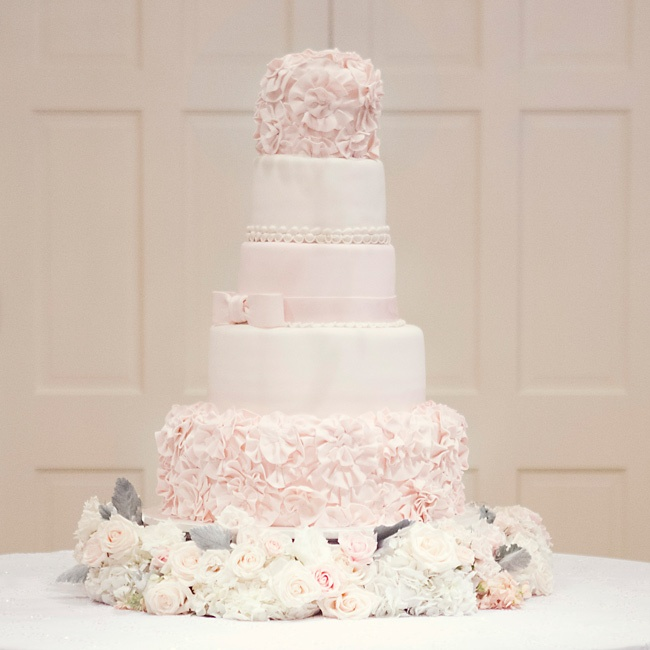 "Brooke, who wanted a feminine cake, describes the blush and off-white confection as ""five layers of pure girl."" The cake included two layers of silver pound cake with butter-bourbon icing, one layer of carrot cake with cream cheese frosting, and one layer of fresh-lemon cake with lemon icing."