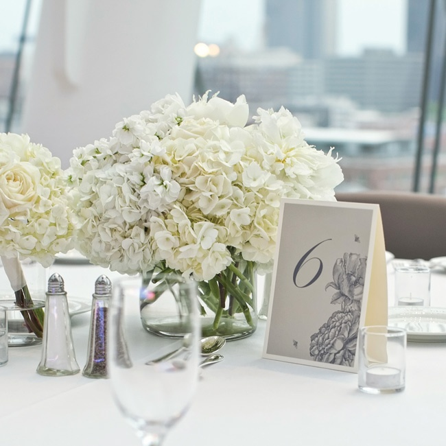 "Centerpieces were large, low arrangements in white and ivory garden blooms including hydrangeas and roses in round, clear glass vases.  ""We went with a low but large arrangement so guests would be able to see across the table and still fill the large tablescape,"" says Jen."