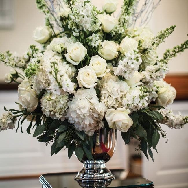 Two large flower arrangements in champagne buckets flanked the state area in the church.  The arrangements included hydrangea, white stock, white roses, white spray roses, white Queen Anne's lace, white larkspur, and filler greens including seeded eucalyptus.