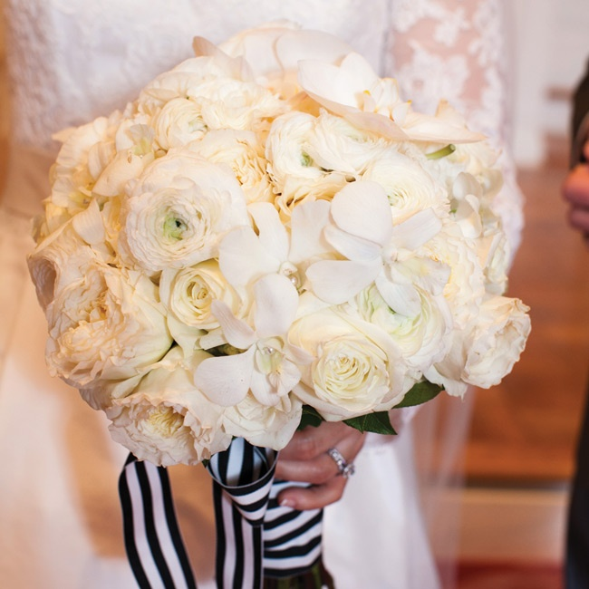 The full bouquet of garden roses, ranunculuses, dendrobian orchids and phalenopsis orchids was hand-tied and wrapped with large striped black and white ribbon with pearl pins.