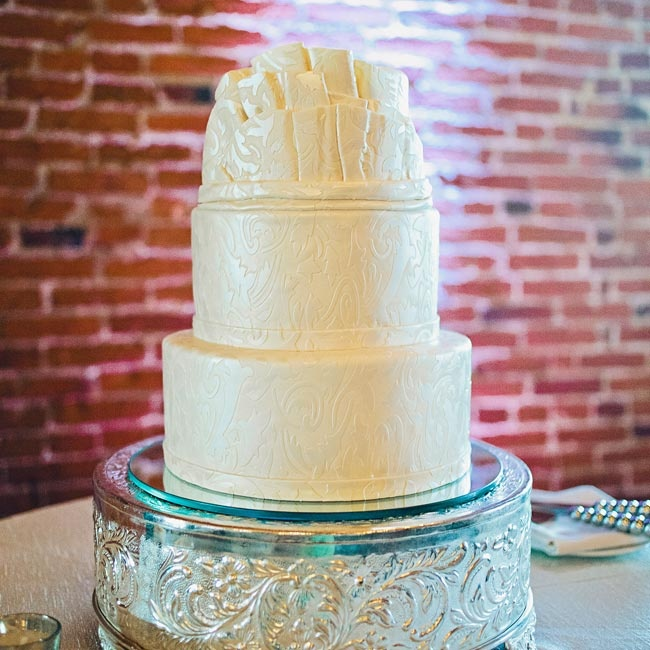 "Look familiar? The design in the fondant was made to look just like Sara's dress. There's even a ""crumb-catcher"" topper!"