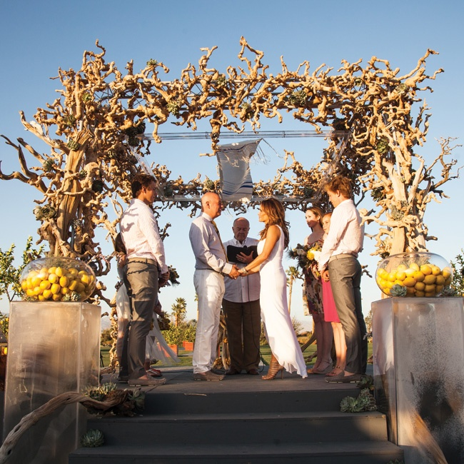 Dana and Joel wanted an understated desert wedding that was, above all, fun. A cheerful palette of lemon yellow, white and gray tied it all together. The color scheme was first introduced at the ceremony, where a huppah was framed in succulents and driftwood—accents which could easily withstand the Palm Springs heat.