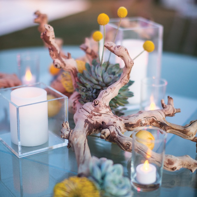 Organic, deconstructed centerpieces of whole lemons, craspedia, driftwood, succulents and votives topped the tables.