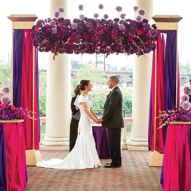 Sofie and Tony were married under a soaring canopy bursting with whimsical flowers and draped in fuchsia and purple fabric.