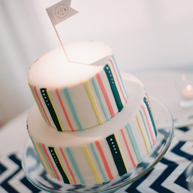 Both layers of their white fondant cake were decorated with cheery vertical stripes to match the wedding colors.