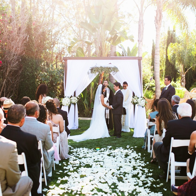 A petal-covered aisle led to the tented wooden
