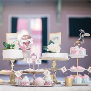 D.S.MeeBee made a cute dessert table that went along with the wedding cake. It had two small frosted cakes and cute cupcakes with pastel colored frosting and decorative wrappers and pastel colored meringue cookies.