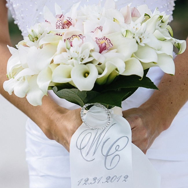 The bouquet of white orchids, mini calla lilies and stephanotis wrapped in a ribbon embroidered with the date and monogram looked modern.