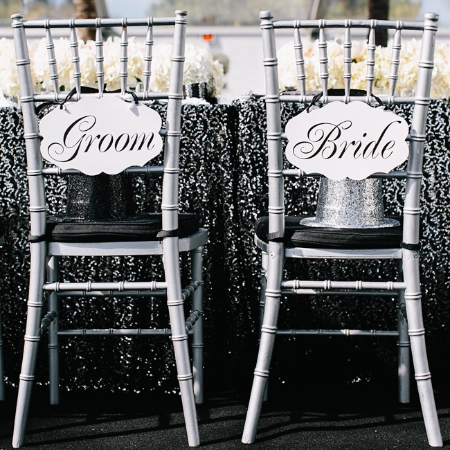 Glittery top hats (for the countdown to 2013) waited for the bride and groom at their seats at the head table. What's a New Year's Eve party without some sparkle? Black linens covered in silver sequins, silver chiavari chairs and white hydrangea centerpieces were 100 percent glitz.