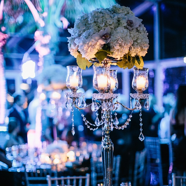 Soaring silver candelabras were topped with all-white arrangements of hydrangeas and cymbidium orchids. Hanging crystals and white votives set the romantic mood for the night ahead.