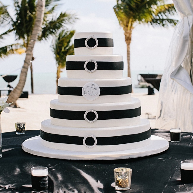 Striking black ribbon decorated the tiers of the classic white cake. A sparkly buckle shone on each layer, save for the middle one, which displayed the couple's monogram.
