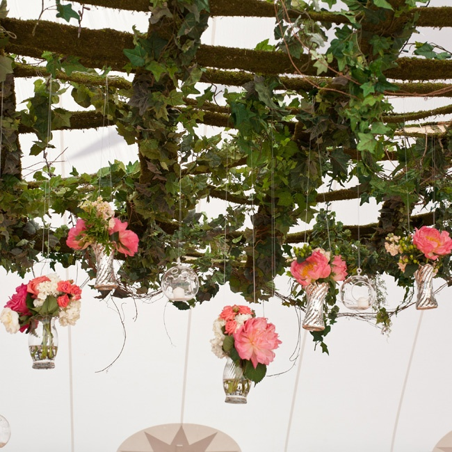 The head table was placed under a portion of the overhead canopy which was strung with flower-filled clear glass vases that hung down just above the table.