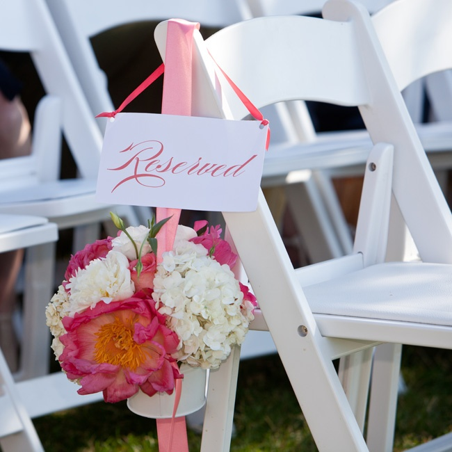 Flowers in white buckets hung at the end of each row under a reserved sign.