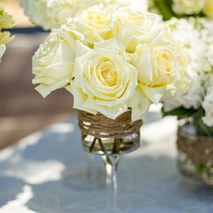 Glass stemware wrapped in twine and filled with white roses and