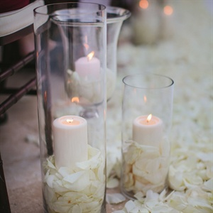 """I had the florist deck out the entire aisle and altar with a bed of petals in white, cream and champagne,"" Sandi says. In addition, cylinder vases with pillar candles set in petals were placed along the aisle to create a soft and romantic glow."