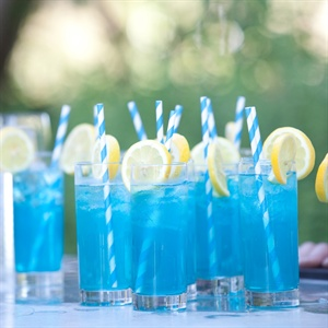 Turquoise striped paper straws were placed in the the signature drink with a lemon garnish on the side.