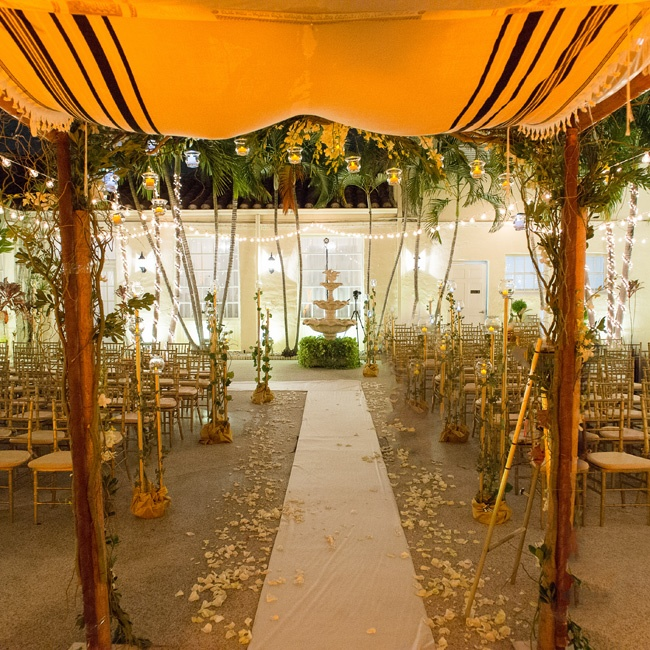 A white aisle runner strewn with rose petals led to a huppah made from their fathers' tallitot.
