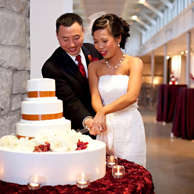 The couple cut into a traditional three-tiered white buttercream cake accented with gold ribbon.