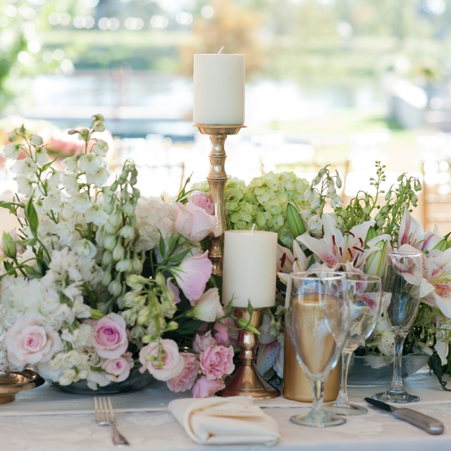 Gathered arrangements of white and pink ranunculus, hydrangeas, roses and lilies were accented with elegant candlesticks.