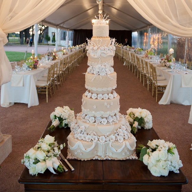 Embellished with pearl piping and white sugar flowers, the couple's seven-tiered wedding cake was covered in fabric-like fondant draping and luxe quilting.