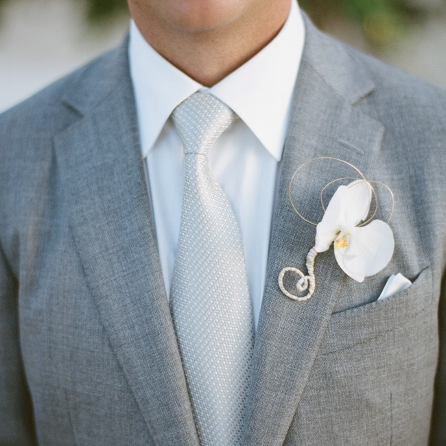 Matt donned a delicate phalaenopsis orchid blossom intertwined with gold wire, adding a touch of white to his pale-gray lapel.