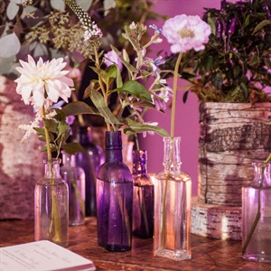 A mix of purple-hued and clear glass bottles with single blooms like roses, astilbes and tweedia decorated the reception entrance.