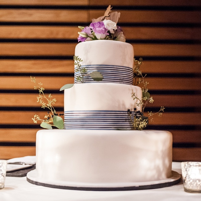 Wrapped with a blue, black and white ribbon, the chocolate truffle cake was finished with a wooden pig and mouse topper to highlight the couple's zodiac-inspired logo.