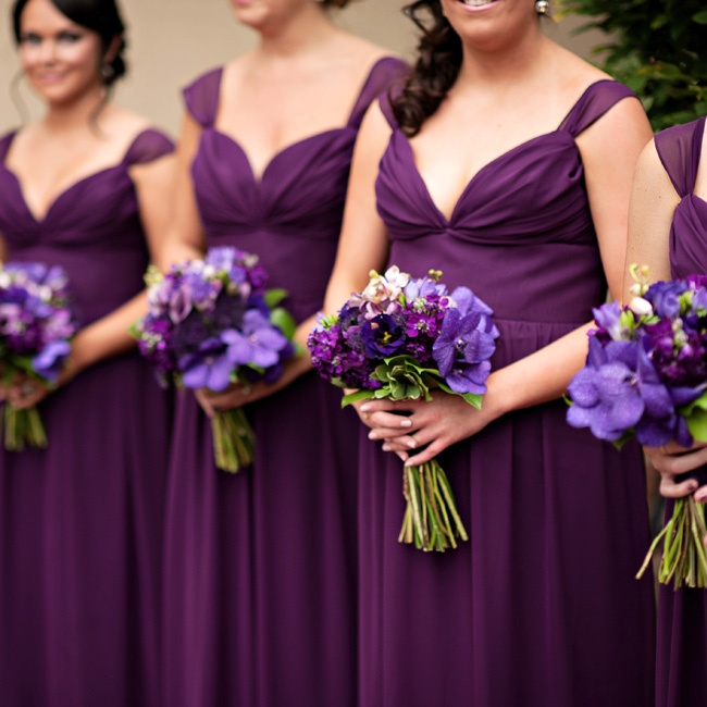 The combination of the violet bridesmaid dresses and their bouquets of purple mokara orchids, stock, lisianthus, trachelium and plum mini calla lilies created a