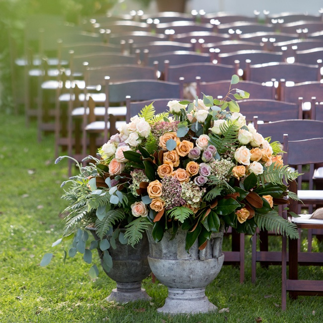 Rustic stone planters filled with fern fronds, greenery and peach, white and lilac roses bookended the outdoor-ceremony aisle.