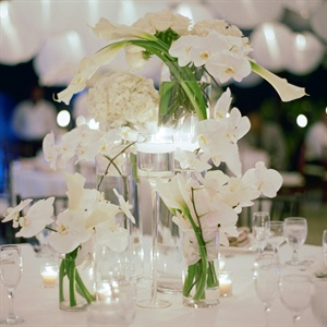 Votives and loose, all-white arrangements of orchids, hydrangeas, roses and calla lilies topped the reception tables.