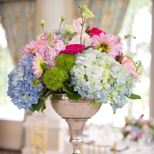High and low centerpieces of blue and white hydrangeas, lisianthus, pink roses, pink and white lupine and hot pink gerbera daisies decorated the reception room and evoked an English garden feel.