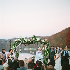 "The lakeside ceremony took place just before sunset under a branch archway decorated with flowers and hanging votive candles. ""I wanted to remember those who had passed. I collected pictures of those family members, put each one in a mason jar with LED candles and hung the jars from the arch,"" Elaine says."