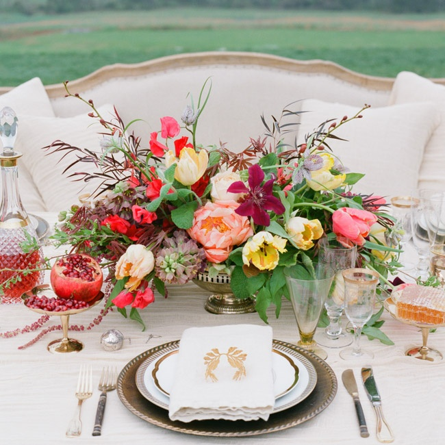 As in the still-life paintings of Raphael and Caravaggio, organic elements such as succulent pomegranates and a colorful centerpiece brighten polished elements such as gold leaf napkin rings. Tabletop, FestiveFareRentals.com; napkin, DeborahRhodes.com; antiques, Birlant.com