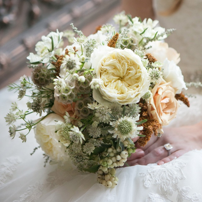 The bride held a rustic bunch of garden roses, thistle and snowberries.