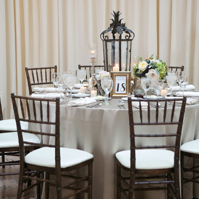 On the reception tables, tall wrought iron lanterns were surrounded by votives, small arrangements and gold-framed table numbers.