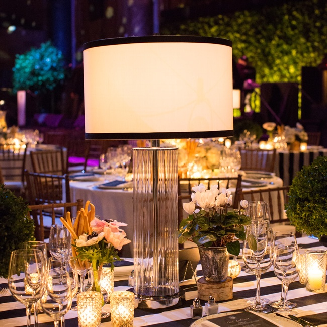 Several tables at the reception were topped with small floral arrangements, votive candles and glass table lamps, which made the space