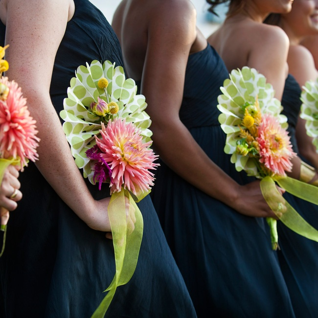 The bridesmaids held paper fans accented with bright dahlias and craspedia—
