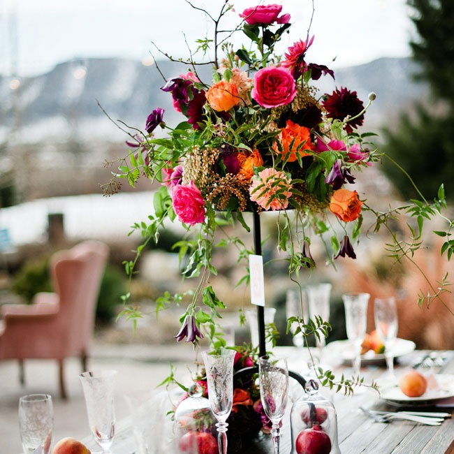 An unstructured grouping of roses, dahlias, French dianthus, andromeda, jasmine, ranunculus and dripping clematis vines keeps this tall arrangement from looking too formal. Cloche domes full of pomegranates tie in the fruit theme.