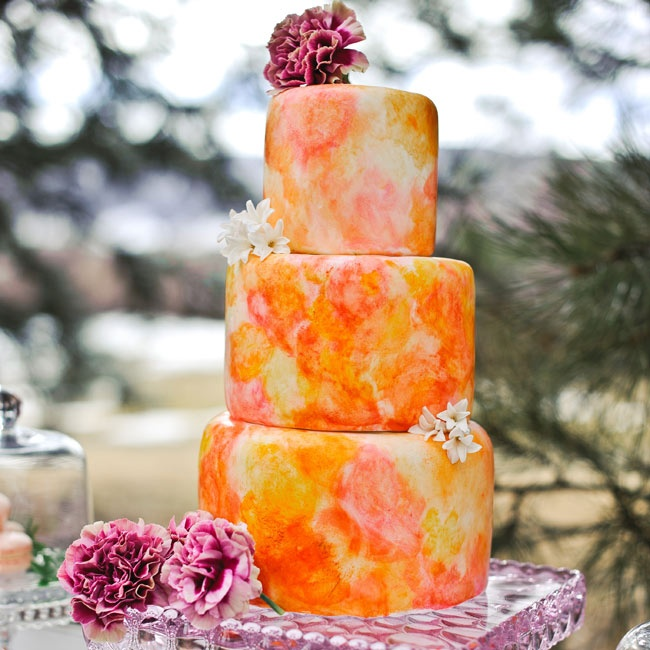Who says your cake needs to be white? A vibrant marbleized pattern like this one is a fun way to tie in your color palette. Forgo expensive sugar flowers and use a few fresh French dianthus and hyacinth florets as decoration.