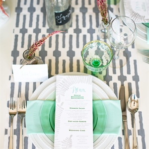 Bold linens, like this graphic runner, are a budget-savvy way to spice up a tablescape. Mismatched antique glass bottles are quintessential touches.