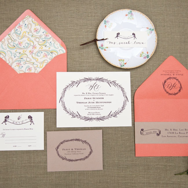 Coral envelopes complement the natural cream and brown tones of the stationery without feeling out of place in the rustic setting. A hand-drawn wreath design is used throughout for a cohesive effect.