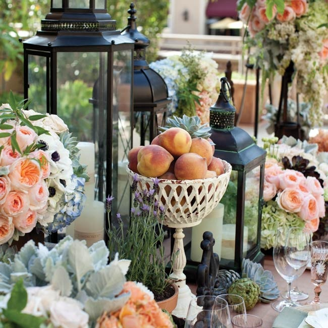 Lush doesn't begin to describe this tablescape of garden roses, white lilac, anemones, dusty miller, succulents, hydrangeas and peaches. Black Hurricane lanterns and white pillar candles look like they were plucked from A Midsummer Night's Dream.
