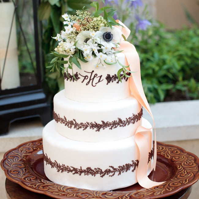 To tie it in with the rest of the day, the white fondant cake was finished with wreath-like chocolate piping mimicking the design from the stationery suite. Fresh blooms and a cascading peach ribbon are romantic touches.